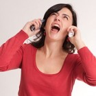Hysterical brunette talking with two telephone receivers